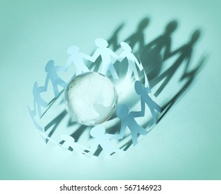 Paper people standing in circle around glass globe