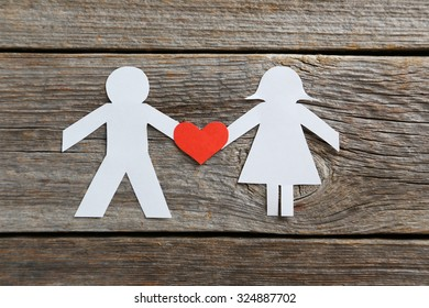 Paper people together in love on the grey wooden background