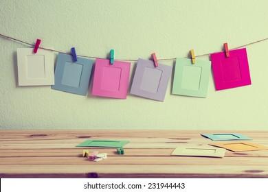 paper photo frame on clothesline over grunge background