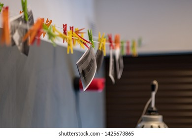 paper photograph drying wire with hooks in analog darkroom with red safelight