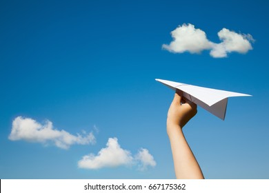 Paper plane in child hand on blue sky and clouds background. (With space for text.)