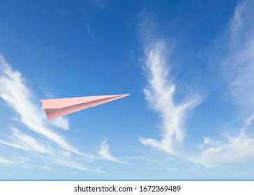 a paper plane flies in a cloudy sky