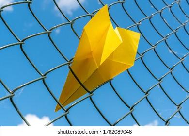 Paper plane gets stuck in metal fence. Cancel flight, delay flight concept.