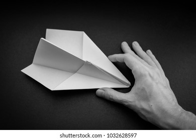 Paper plane in hand on dark background.