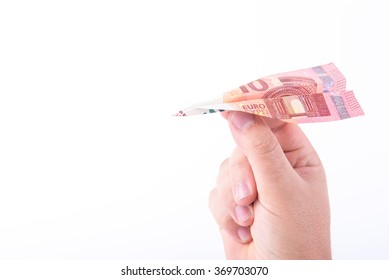 Paper plane made with a bill of 10 euros and a hand getting ready to make it fly on white background