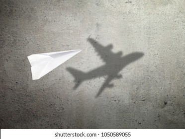 Paper plane in mid flight with shadow of a real plane