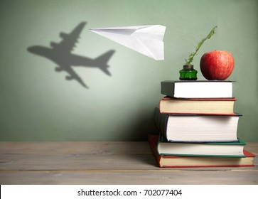 Paper plane with shadow of an aircraft next to a stack of books, quill and apple
