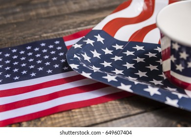 Paper plate and cup with American flag set up on wooden table, background