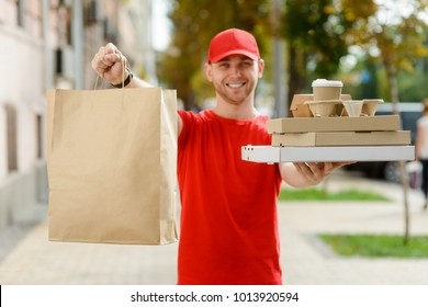 Paper pocket and food containers in hands of a smiling deliveryman outdoors. Quality service of a restaurant.