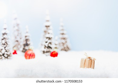 Paper present box in snow winter landscape with Christmas ornament decoration background, financial savings concept