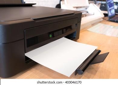 Paper printer on work table background. Digital laser sticker print technology machine.