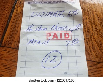 paper receipt with word paid and ham and cheese sandwich and dollar amounts