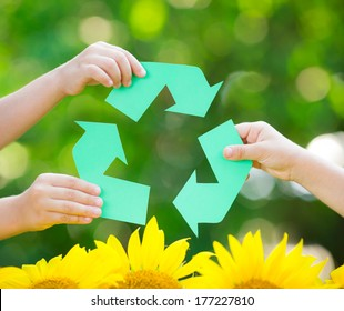 Paper RECYCLE sign in hands against green spring background. Earth day concept