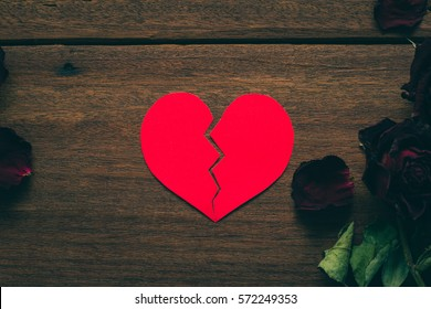 Paper Red broken heart with dry roses on wooden background. Black Valentine's Day.