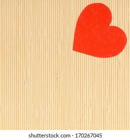 Paper red heart love symbol on beige bamboo mat copy space for text as valentine's day concept