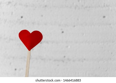 Paper red heart that sympholise love and passion on the left on a white blurred background. Valentines card