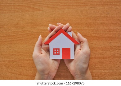 Paper red roof house in two hand on wood background,protecting home concept.