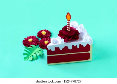 Paper red velvet cake with burning candle and cream. Volumetric handmade paper objects. Paper art and craft. Trendy hobby. Minimal art food concept