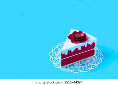 Paper red velvet cake. Piece of cake on openwork napkin. Volumetric handmade paper objects. Paper art and craft. Trendy hobby. Minimal art food concept. Copy space