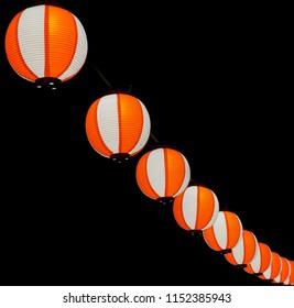 Paper red-white asian japanese chinese lanterns chochin akachochin shines on dark sky. A garland of paper lanterns glows at night