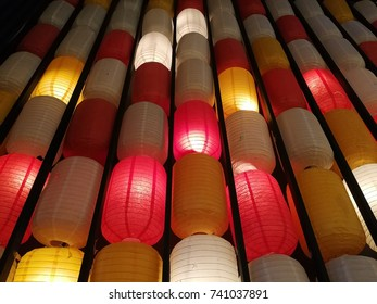 Paper red-white japanese lanterns Chochin shines on the wall.