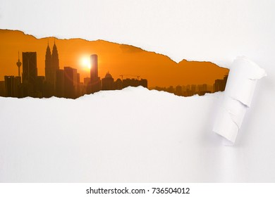 Paper rip unveiling Kuala Lumpur skylne during sunset. Reveal concept.