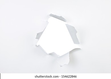 Paper with ripped hole and torn edges over white