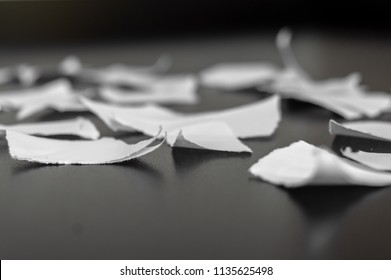 Paper ripped in many pieces over a black surface