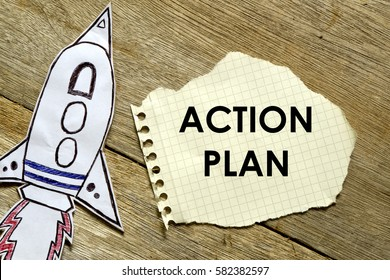 Paper rocket with paper written ACTION PLAN on wooden background. Business concept
