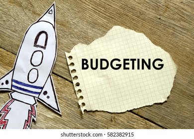 Paper rocket with paper written BUDGETING on wooden background. Business concept