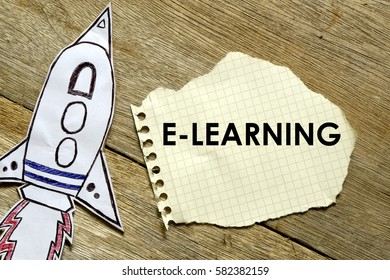 Paper rocket with paper written E-LEARNING on wooden background. Business concept