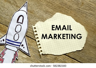 Paper rocket with paper written EMAIL MARKETING on wooden background. Business concept