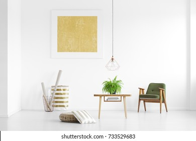 Paper rolls in metal basket and green armchair in white room with yellow poster