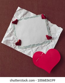paper scraps with red shape of heart on cardboard