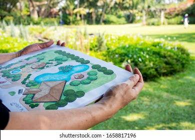 paper sheet of layout plan with hands and garden background, that shown design of clubhouse landscape or garden design   drawing by hand with color marker pens and color pencil, selective focus