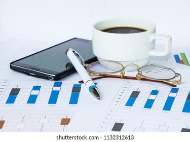 paper sheets of a business plan, a pen, a cup of coffee, and sma