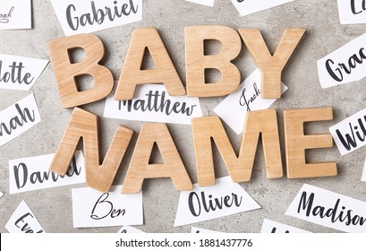 Paper sheets with different baby names and wooden letters on grey background, flat lay