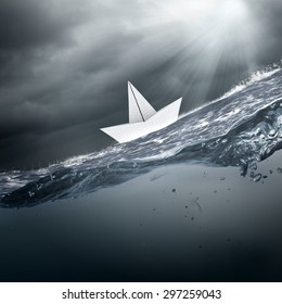Paper ship floating on water on stormy waves