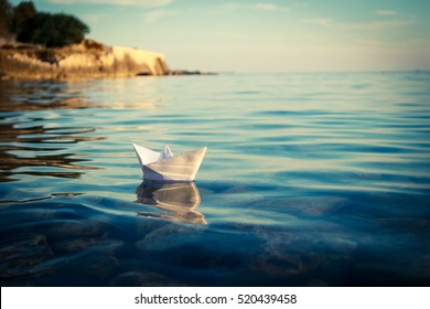 Paper Ship Floating in the Sea. Origami Paper Boat Sailing. Beautiful Waves Ripple Background. Unusual Travel Concept. Toned and Filtered Photo with Copy Space.