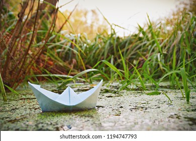 Paper ship floats between autumn leaves in a low-flowing water - Colorful paper ship in autumn in the water