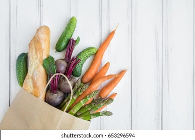 Paper shopping bag with fresh bread, carrots, cucumbers, asparagus and beet. Eco shopping concept, products for cooking. Flat lay on white vintage wooden table. Top view with place for text