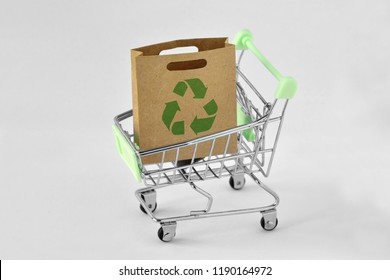 Paper shopping bag with green recycle symbol in shopping cart - Ecology concept