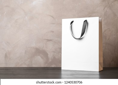 Paper shopping bag with handles on table against color wall. Mock up for design