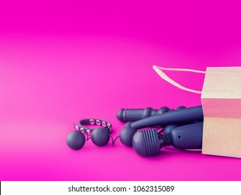 A paper shopping bag is placed on a background of fuchsia. Inside the package are various sex toys. Image for sex shop advertising, promotion on the Internet, discounts and sales, email newsletters
