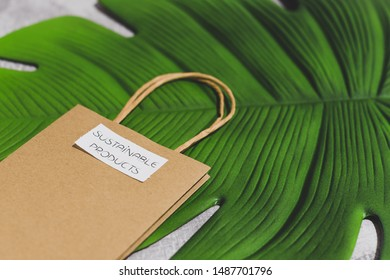 paper shopping bag with Sustainable Item label on it on leaf and concrete background, concept of making eco-friendly purchases