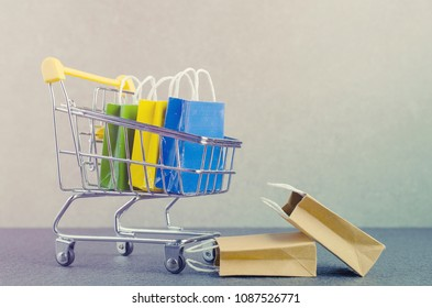 Paper shopping bags  in a shopping cart on granite floor and grey wall,e-commerce or electronic commerce is a transaction of buying or selling goods or services online over the internet.