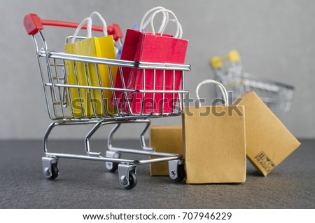 91303ec96 Paper shopping bags in a shopping cart on granite floor and grey wall