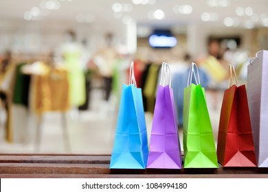 Paper shopping bags with shopping and gift, on the floor against with blurred clothes shop for display or montage your products