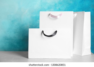 Paper shopping bags on table against color background. Mock up for design