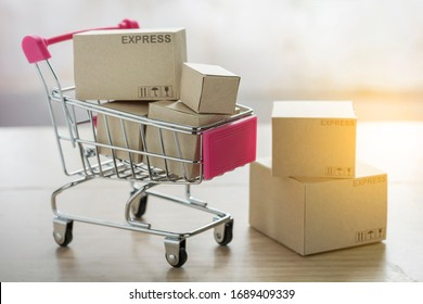 Paper shopping small box express in a shopping cart on wood table background. Online shopping concept.